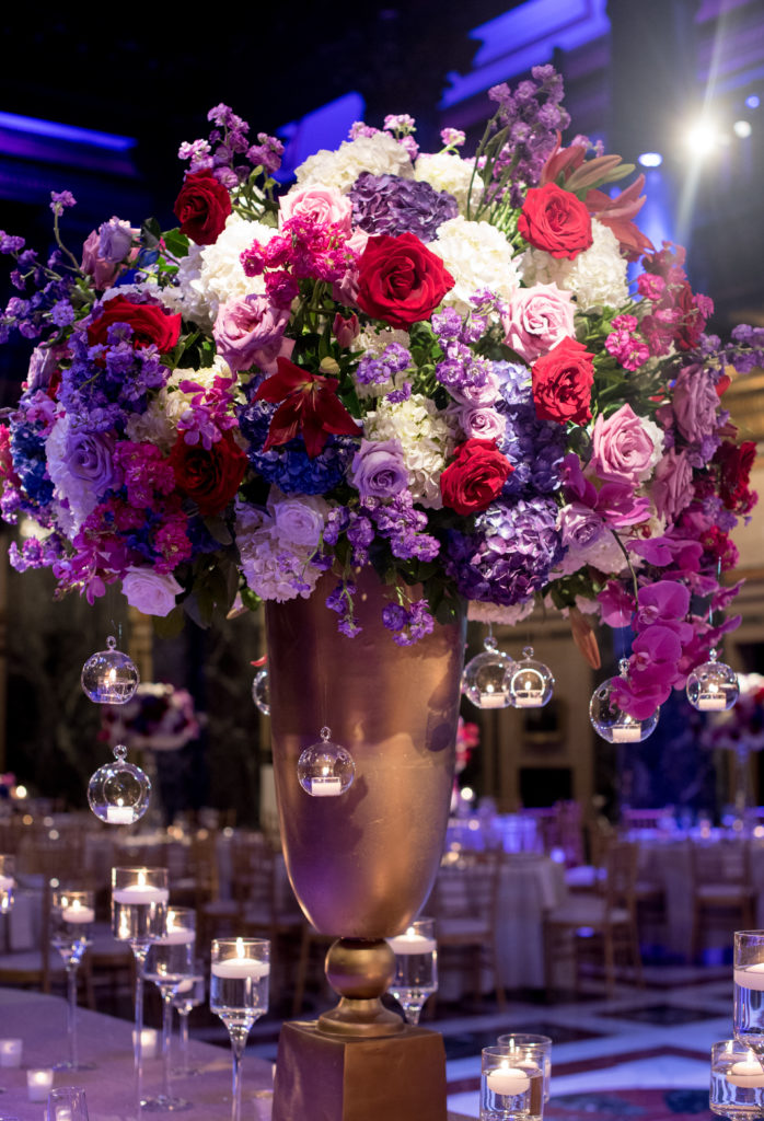 statement centerpiece details large floral arrangement jewel tones gold urn hanging candles
